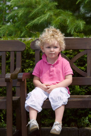 cute young boy sitting on a bench in summer photo