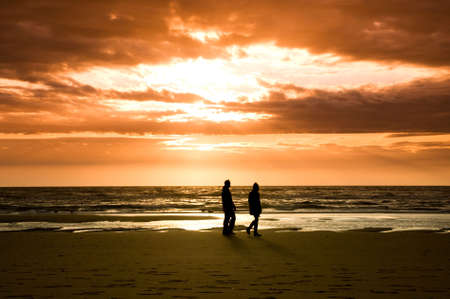 couple walking on the beach with beautiful sunset and waves