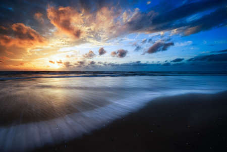 Sonnenuntergang und Wellen am Strand