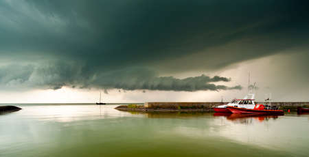 ijsselmeer: A storm cloud approaching in the harbor of a small village called Laaksum on the IJsselmeer in The Netherlands