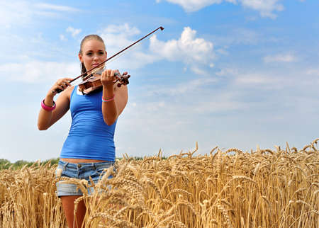 young attractive woman playing the violin in the country photo