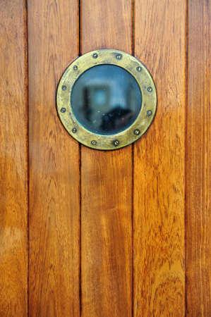 eine antike Tür mit Bullauge von einem Schiff Lizenzfreie Bilder