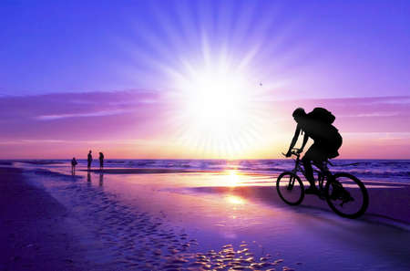off road biking: silhouette of a mountain biker on beach and sunset