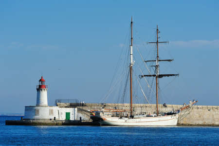 Lighthouse and sailboat in the harbor of Ibiza town, Ibiza Spain photo