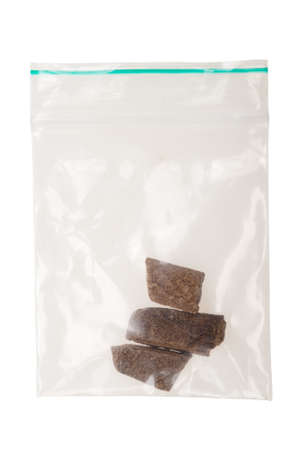 sealable: pieces of hashish in a plastic bag , Photo taken with a macro lens,  isolated on a white background
