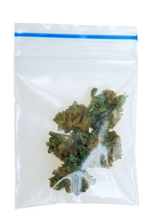Bolsa de marihuana en un plástico, tomada con una lente macro, aislado en un fondo blanco  Foto de archivo