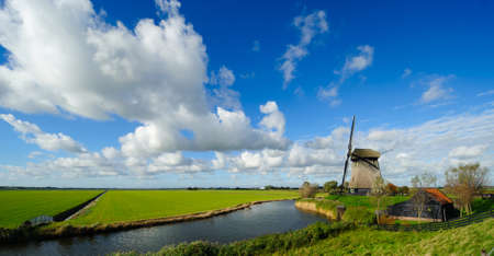 beautiful windmill landscape in the Netherlands, Schermerhorn, Schermer, Noord-Holland  Фото со стока