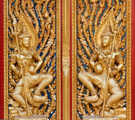 Sculpture wood beautyful entrance gate of Buddhist temple in Thailand photo