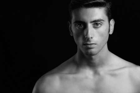 seductive look: portrait of man in black and white on a black background
