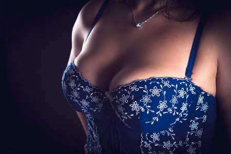 tetas: tetas en un cors� azul sobre fondo negro