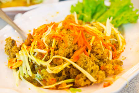Spicy fried Thai tilapia fish salad minced meat with vegetable,thai food photo