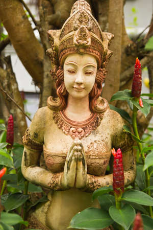 Face of stone old brown  female statue with gentle smile,Thailand  photo