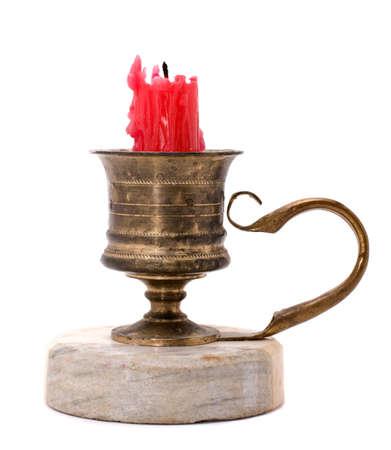 Antieke koperen kandelaar met rode kaars-end geïsoleerd