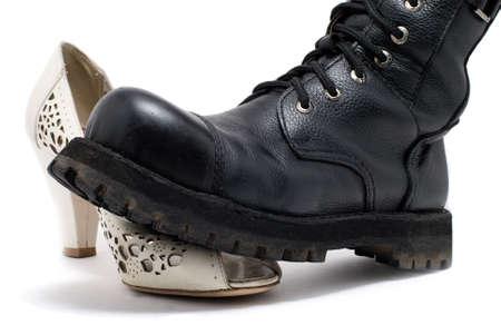 Black military shoe on white women's shoes on a white background  Stockfoto