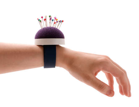 Purple pincushion bracelet with pins on the wrist,  isolated on white