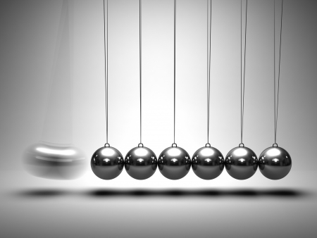 Balancing balls Newtons cradle on grey background Stock Photo