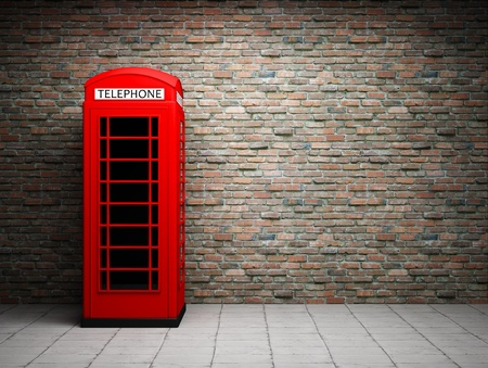 old english: Classic red telephone booth at the brick wall Stock Photo
