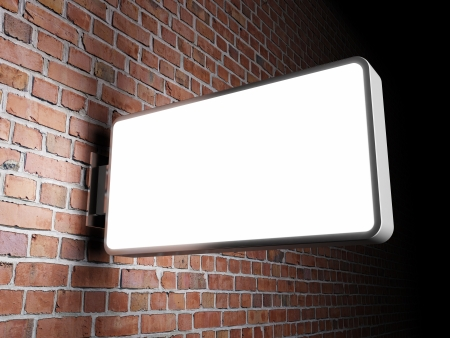 Blank advertising billboard on brick wall at night photo