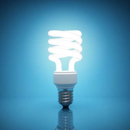 bombillo: Bombilla de luz iluminada sobre fondo azul