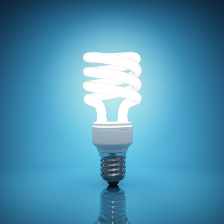 Illuminated light bulb on blue background photo