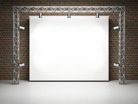 an exposition: Fiera stand con schermo in bianco e faretti sul muro di mattoni