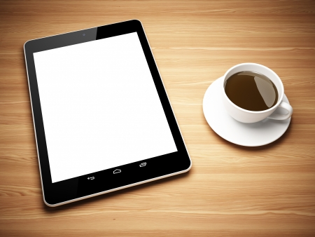 Black tablet computer and cup of tea on wooden table photo
