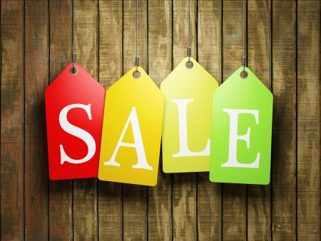 Colorful sale tags hanging on wooden background