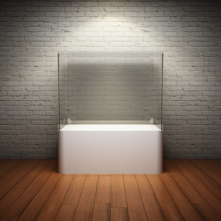 pedestal: Empty glass showcase for exhibit in interior room with brick wall and spotlight