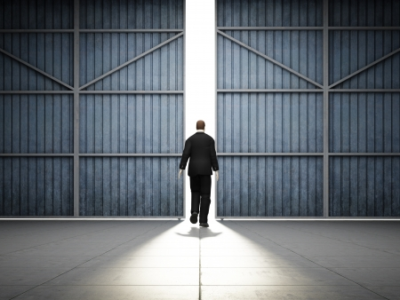 Man walks into light of large hangar doors photo