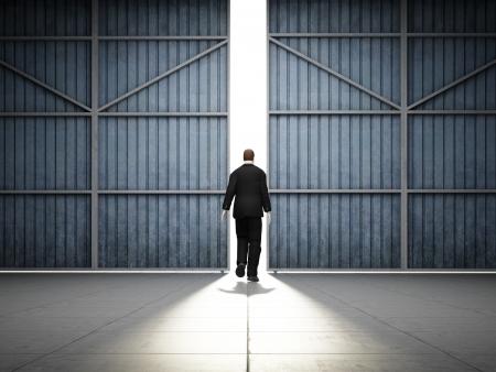 large doors: Man walks into light of large hangar doors