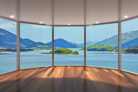 views of the mountains: Empty modern lounge area with large bay window and view of sea