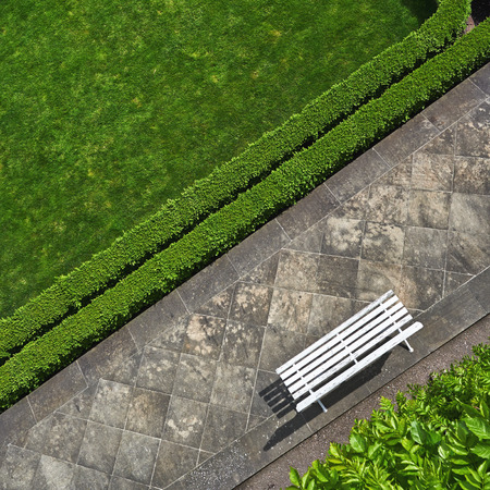Geometric background with a white bench in a green park. Top view photo