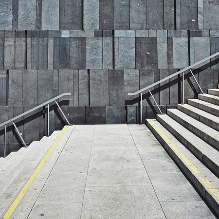 geometric modern wall with stairs leading up. square background photo