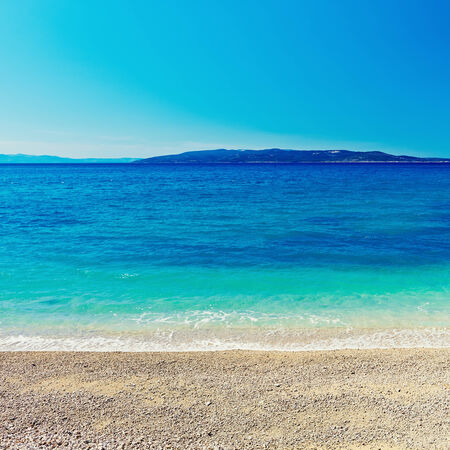 Pebble Beach: Amazing sea bay blue background Stock Photo