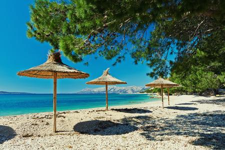 Piękna pusta plaża z krystalicznie czystą wodą i parasole w Chorwacji
