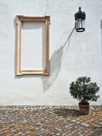 Old shabby white wall with blank frame, lamp and a plant in a flowerpot on the street photo