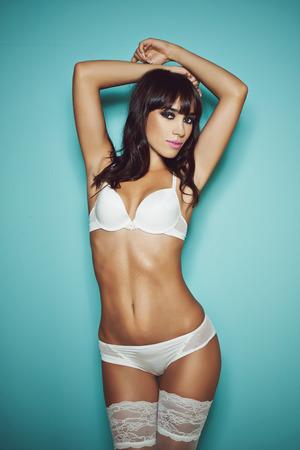 desnudo de mujer: Hermosa morena sexy en ropa interior blanca aislada en un fondo azul Foto de archivo