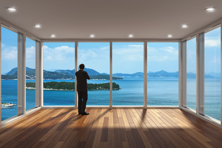 windows home: Businessman standing in modern lounge area with large bay window and view of sea
