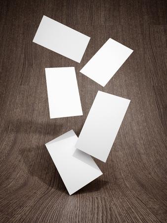 Business card falling on wooden background. 3D illustration.