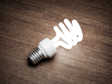 Illuminated light bulb on wooden table. 3D illustration. Banque d'images - 101220928
