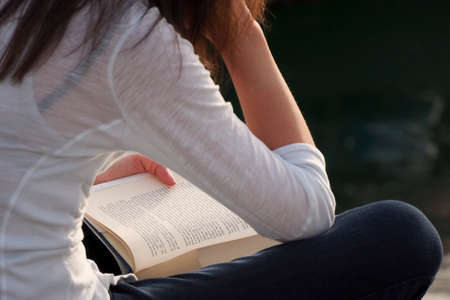 legs crossed on knee: A girl is reading a book in the open air