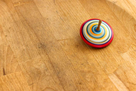 wooden handmade: Traditional toy. A wooden spinning-top in action on a wooden handmade table. Stock Photo