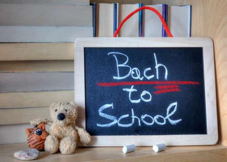 syntax: Word bach instead of back in the writing Back to school on a wooden chalkboard. Error underlined in red.