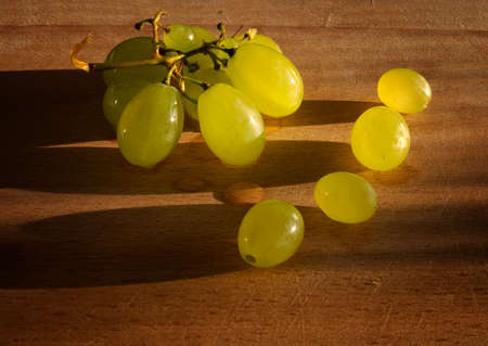 sidelight: Summer fruit, grapes on wooden table in a warm natural light.