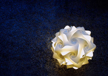 A domestic lamp, in the shape of a flower, turned on and placed on a dark blue carpet. Minimalistic composition.