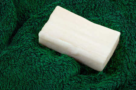 hand towel: Bar of soap on a green hand towel.
