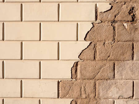 removed: A portion of a wall made of bricks with removed plaster in the right side.