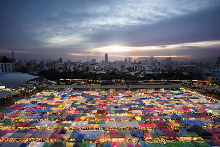 Multi-color tents at the train night market in Bangkok Thailand,with tons of food stalls grilled seafood snacks, people selling all kinds of merchandise at some good prices (clothes vintage stuff )and bars line the perimeter, music in some places.