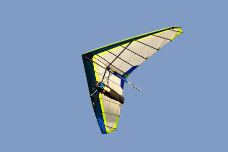currents: hang glider in soaring flight off lookout mountain,isolated on light blue.  A glider in flight is continuously descending. the pilot must seek air currents rising Stock Photo