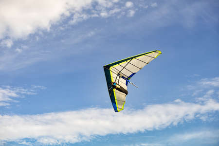 hang glider in soaring flight off lookout mountain at Bald Hill Stanwell Par, Australia.  A glider in flight is continuously descending. the pilot must seek air currents rising